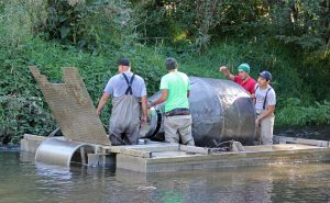 adults adjusting large water instrument in creek