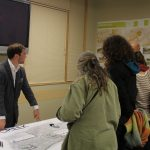 adults looking at large Mill Creek map