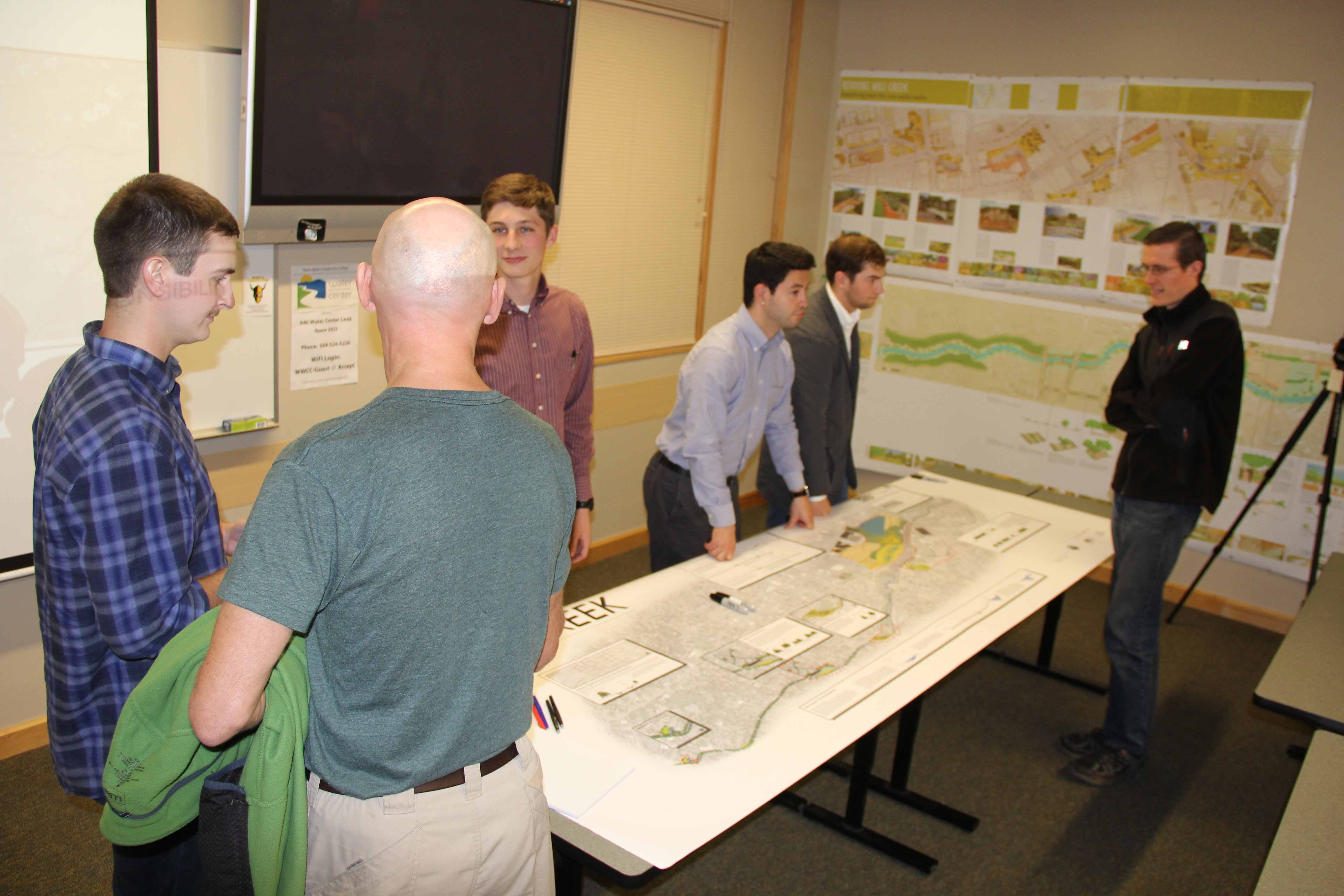 adults looking at large map of Mill Creek