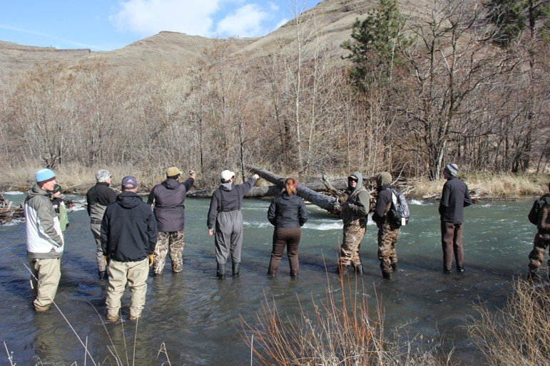 staff and students in shallow creek pointing at hill